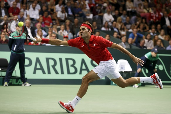 epa04397090 Roger Federer of Switzerland, returns a ball to Simone Bolelli of Italy, during the first single match of the Davis Cup World Group Semifinal between Switzerland and Italy, at Palexpo, in Geneva, Switzerland, 12 September 2014.  EPA/SALVATORE DI NOLFI