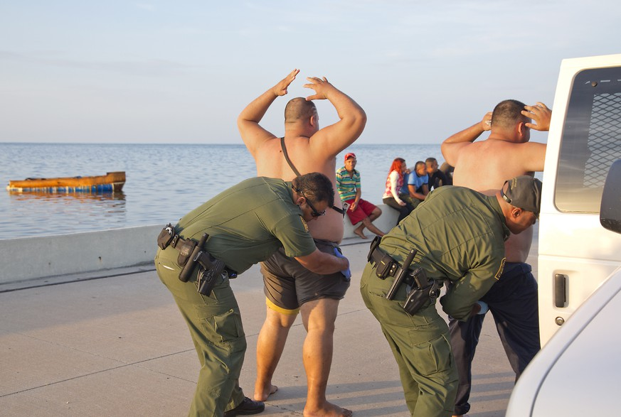 U.S. Customs and Border Protection officers frisk two of 24 Cuban migrants that came ashore in Key West, Fla., on Monday, Aug. 3, 2015. The group of 23 men and one woman said they left Cardenas, Cuba, 24 hours earlier aboard a 20-foot handmade boat, powered by an 8-cylinder truck motor according to the Key West Citizen.  (Rob O'Neal /The Key West Citizen via AP)  MIAMI OUT; MANDATORY CREDIT