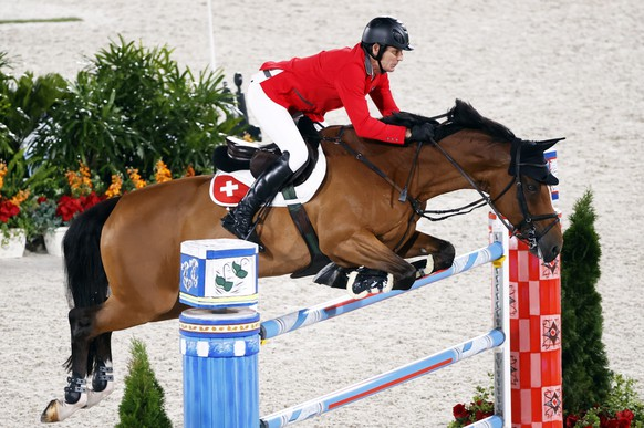 epa09392071 Beat Mandli of Switzerland on Dsarie competes in the Jumping Individual Qualifier during the Equestrian events of the Tokyo 2020 Olympic Games at the Baji Koen Equestrian Park in Setagaya, Tokyo, Japan, 03 August 2021.  EPA/MICHAEL REYNOLDS