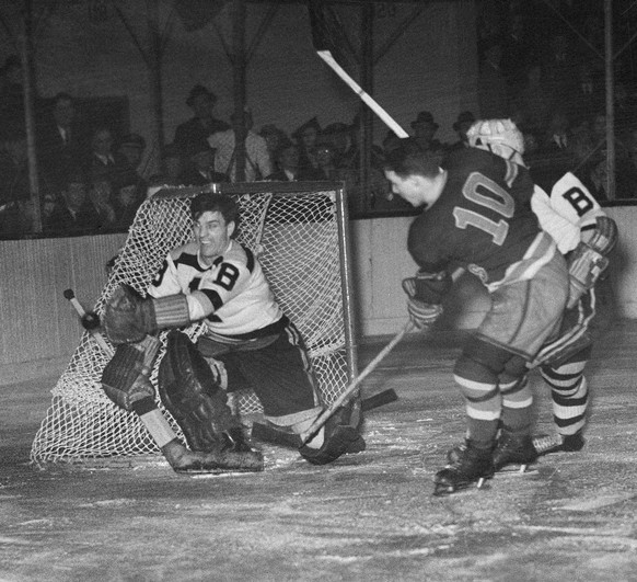 In this March 21, 1939, photo, Boston Bruins goalie Frankie Brimsek sends the puck out of the danger zone after he stopped a New York Rangers threat by Clint Smith (10) in the third period of the opening game of their Stanley Cup playoff series in Madison Square Garden in New York. Smith, a two-time winner of the Lady Byng Trophy while with the Chicago Blackhawks and the Rangers, died Tuesday, May 19, 2009. He was 95. (AP Photo)
