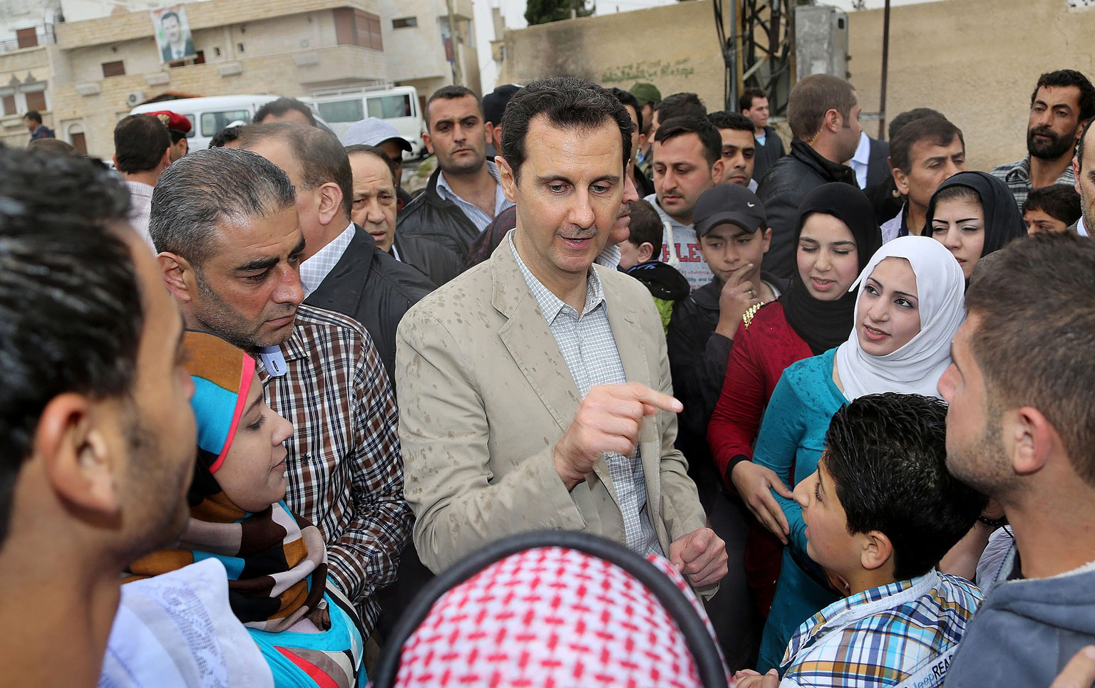 epa04174373 A handout picture made available by the official government Syrian Arab News Agency (SANA) shows Syrian president Bashar al-Assad (C) during his visit to the predominantly Christian city of Maaloula, Syria, 20 April 2014. Syrian President Bashar al-Assad marked Easter by visiting a Christian town near Damascus recently recaptured by his forces, state media reported. Al-Assad's government has frequently portrayed itself as protecting Syria's religious minorities, a portrayal aided by the increasing dominance of hardline Islamist groups and jihadists in the armed opposition.  EPA/SANA / HANDOUT  HANDOUT EDITORIAL USE ONLY/NO SALES