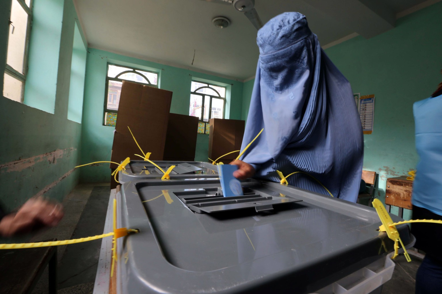 epa04154985 An Afghan woman casts her ballot at a polling station during the Presidential elections in Herat, Afghanistan, 05 April 2014. Afghanistan began voting 05 April, for a new president amid fears of violence and insecurity. About 12 million voters are eligible to cast ballots at some 6,400 polling centers across the country, according to IEC. Around 400,000 security forces have been deployed.  EPA/JALIL REZAYEE