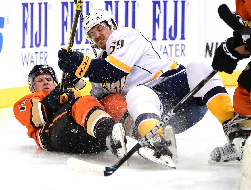 ANAHEIM, CA - NOVEMBER 01:  Corey Perry #10 of the Anaheim Ducks and Roman Josi #59 of the Nashville Predators fall to the ice during the first period at Honda Center on November 1, 2015 in Anaheim, California.  (Photo by Harry How/Getty Images)