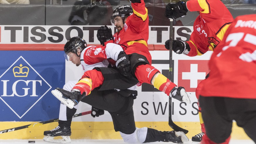 Malmoe's Carl Persson, left, fights for the puck with Bern's Mark Arcobello, center, and Justin Krueger during the Champions Hockey League round of 16 second leg match between SC Bern and Malmoe Redhawks, in Bern, Switzerland, Tuesday, November 20, 2018. (KEYSTONE/Alessandro della Valle).