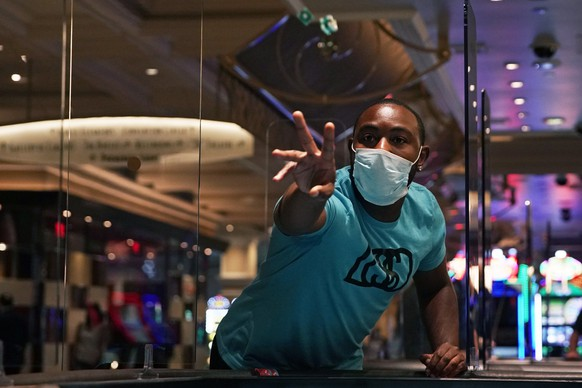 A man plays craps at the reopening of the Bellagio hotel and casino Thursday, June 4, 2020, in Las Vegas. Casinos in Nevada were allowed to reopen on Thursday for the first time after temporary closures as a precaution against the coronavirus. (AP Photo/John Locher)