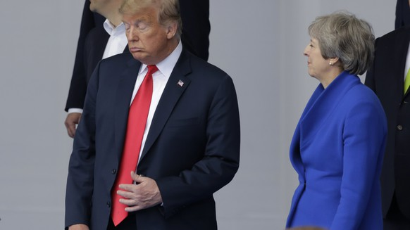 U.S. President Donald Trump, left, talks to British Prime Minister Theresa May during a family photo at a summit of heads of state and government at NATO headquarters in Brussels Wednesday, July 11, 2018. NATO leaders gather in Brussels for a two-day summit to discuss Russia, Iraq and their mission in Afghanistan. (AP Photo/Markus Schreiber)