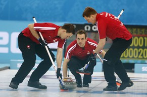 Switzerland's skip Sven Michel, center, delivers the rock to his sweepers Sandro Trolliet, left, and Simon Gempeler in a men's curling game against Sweden at the 2014 Winter Olympics, Monday, Feb. 10, 2014, in Sochi, Russia. (AP Photo/Robert F. Bukaty)