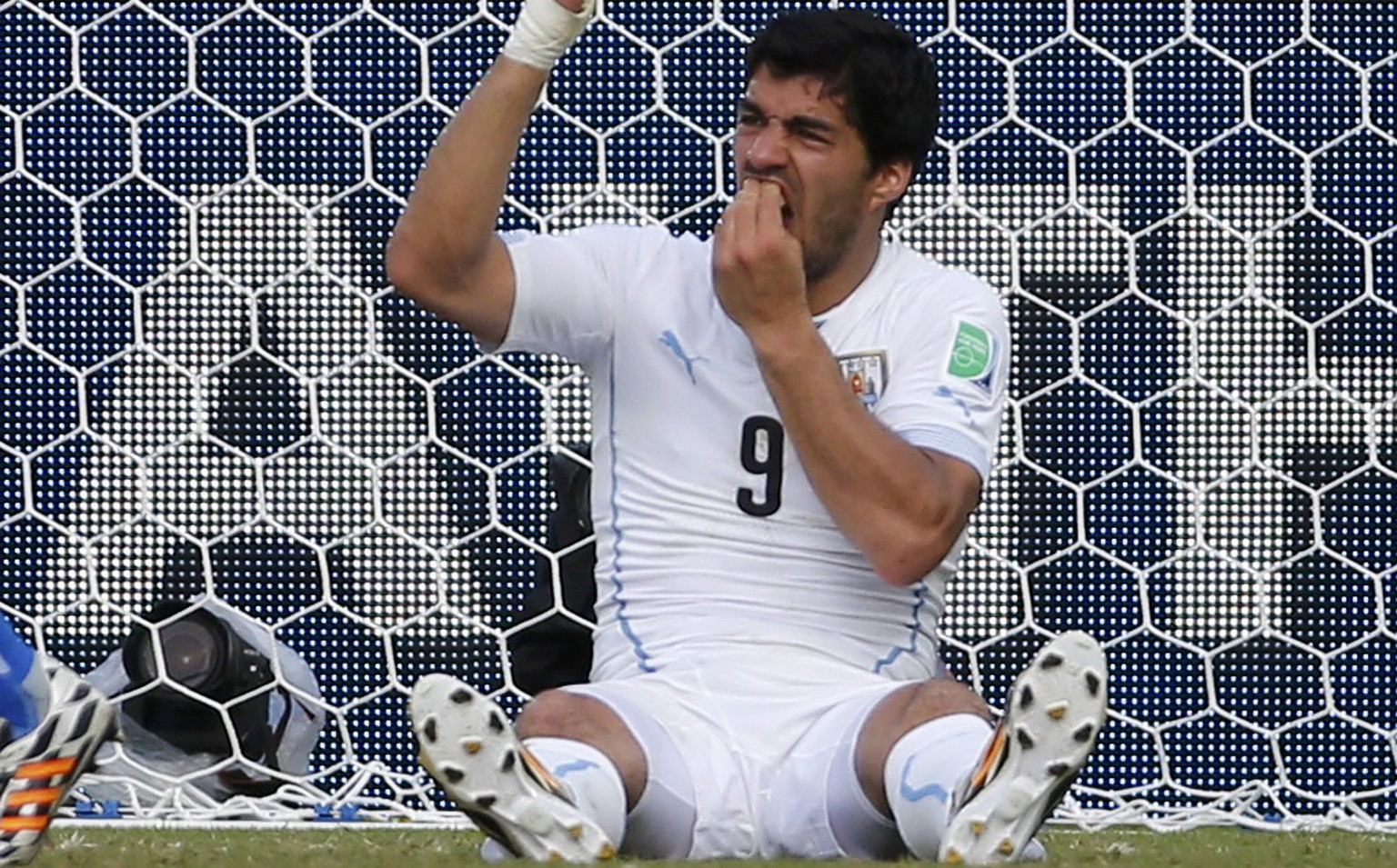 Uruguay's Luis Suarez holds his teeth during the 2014 World Cup Group D soccer match between Uruguay and Italy at the Dunas arena in Natal June 24, 2014. Italy's Giorgio Chiellini accused Suarez of biting his shoulder. REUTERS/Yves Herman (BRAZIL  - Tags: TPX IMAGES OF THE DAY SOCCER SPORT WORLD CUP)