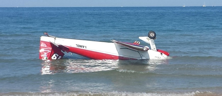 One of the two aircrafts part of an aerobatic team, which collided while performing, lies in the water near the beach in Tortoreto, Italy, Sunday, May 31, 2015. Two single-seat acrobatic planes collided during a show in the sky near Italy's Adriatic shore and crashed into the sea, killing one pilot and injuring the other. (Giuseppe De Dominicis/ANSA via AP) ITALY OUT