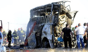 epa04060867 Firemen are seen close to a burned bus at a highway in Mendoza province, eastern Argentina, 07 February 2014. At least 17 people died and more than 12 were injured in a crash between a bus and an oncoming truck, according to official sources. The accidente happened on the Route Seven close to San Martin locality, eastern Mendoza.  EPA/ALFREDO PONCE