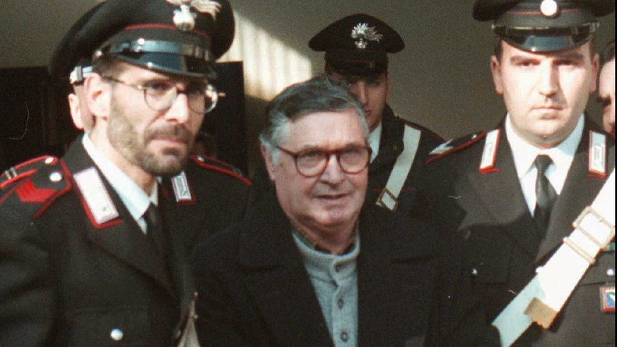 FILE - In this Jan. 16, 1996 file photo, Mafia ''boss of bosses'' Salvatore ''Toto'' Riina, center, enters handcuffed into Bologna's bunker-courtroom, escorted by Carabinieri, Italian paramiliary police, in Bologna, Italy. Italy's justice minister has given special permission for family bedside visits to the comatose top Mafia boss. Italian media said Riina's health deteriorated recently after undergoing two recent surgeries. (AP Photo/Gianni Schicchi)