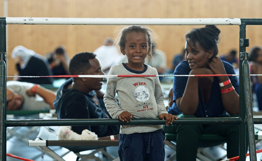 epa04873796 A picture made available 06 August 2015 shows shows a family from Eritrea in a gymnasium on the grounds of the German Federal Police in Rosenheim, Germany, 04 August 2015. German police picked up around 150 refugees from various countries from an inbound train from Verona. After being searched and registered, they received an identification document at an office of the German Federal Police and were sent to the refugee reception facility in Munich where they may apply for asylum.  EPA/ANDREAS GEBERT
