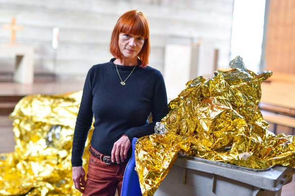 epa05141087 Artist Romana Menze-Kuh stands by her piece 'Behausung 6/2016' (Housing 6/2016) in a church in Mannheim, Germany, 03 February 2016. A cleaner accidently threw a piece of the space blanket into the trash. The artist is using the incident by incorporating the trash can into her work.  EPA/UWE ANSPACH