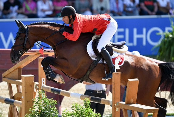 epa04852243 Swiss rider Steve Guerdat on his horse 'Corbinian' clears an obstacle during the 100th Nations Cup of Germany international show jumping event at the Equestrian stadium in Mannheim, Germany, 18 July 2015. Organizers expect thousands of spectators in the stadium for this CSIO - Concours de Saut International Officiel event from 16 to 19 July 2015.  EPA/UWE ANSPACH