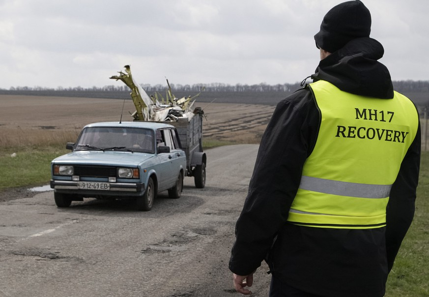 epa04707275 An investigator looks to a car which transports the parts of the wreckage of Malaysia Airlines passenger jet MH17 near Donetsk, Ukraine, 16 April 2015. The Malaysian Airlines plane, which was flying from Amsterdam to Kuala Lumpur, was shot down over Ukraine in July. All 298 people on board were killed.  EPA/ALEXANDER ERMOCHENKO