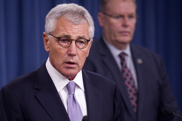 Defense Secretary Chuck Hagel, left, accompanied by Deputy Defense Secretary Bob Work, briefs reporters at the Pentagon, Wednesday, Oct. 1, 2014, on the military health care system. (AP Photo/Cliff Owen)
