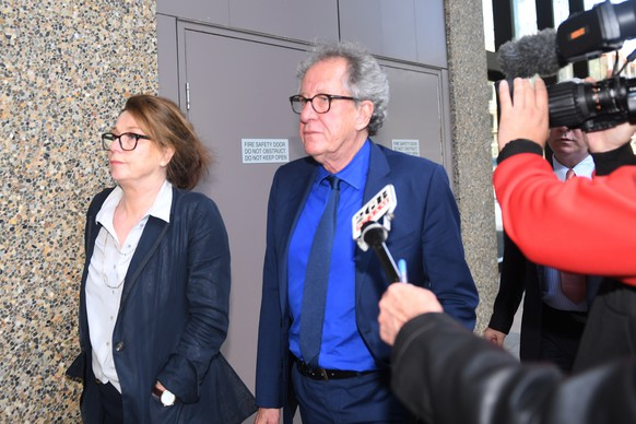 Australian actor Geoffrey Rush, center, leaves the Federal Court in Sydney, Australia Monday, Oct. 22, 2018. The actor faced a large media pack Monday as he entered Sydney's Federal Court, where a judge is hearing his defamation trial against Sydney's Daily Telegraph and its journalist Jonathon Moran. (Dean Lewins/AAP Image via AP)
