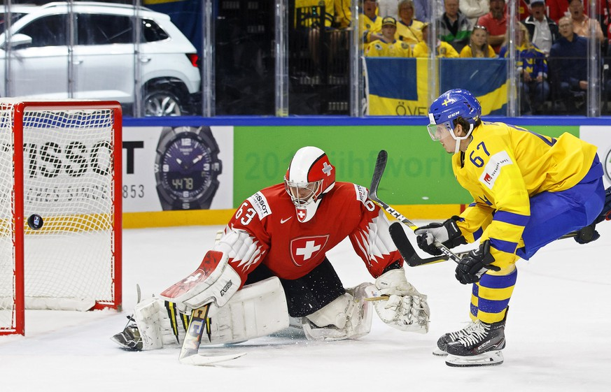 epa06733881 Sweden's forward Rickard Rakell (R) in action against Switzerland's goalie Leonardo Genoni (L) during the IIHF World Championship Group A ice hockey match between Switzerland and Sweden at the Royal Arena in Copenhagen, Denmark, 13 May 2018.  EPA/SALVATORE DI NOLFI