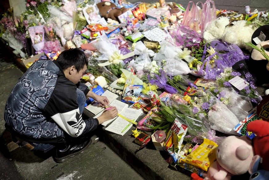 A man leaves a message on a memorial book at a makeshift memorial near the site where a girl was found decapitated, outside a metro station, in Taipei, Taiwan March 28, 2016. REUTERS/Tyrone Siu