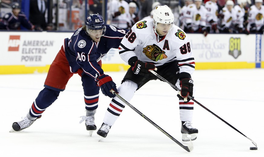 Chicago Blackhawks' Patrick Kane, right, keeps the puck away from Columbus Blue Jackets' Dean Kukan during the first period of an NHL hockey game Saturday, April 9, 2016, in Columbus, Ohio. (AP Photo/Jay LaPrete)