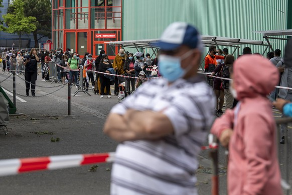 epa08439100 People queue to receive bags with free food and essential products received from donations at the ice stadium Les Vernets, in Geneva, Switzerland, 23 May 2020. The ongoing coronavirus COVID-19 pandemic casts a spotlight on the usually invisible poor people of Geneva.  EPA/MARTIAL TREZZINI