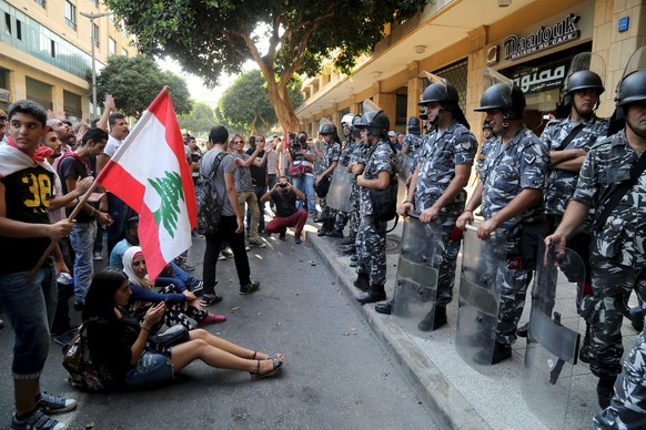 Protestors carry a Lebanese flag in front of riot police at one of the entrances to the environment ministry in downtown Beirut, Lebanon September 1, 2015. Dozens of protesters occupied the environment ministry in the Lebanese capital Beirut on Tuesday calling on minister Mohamad Al Machnouk to resign over a rubbish disposal crisis, the latest in a wave of protests against the paralysed political system. Hundreds of other protesters gathered outside the building as riot police took up positions in surrounding streets and the