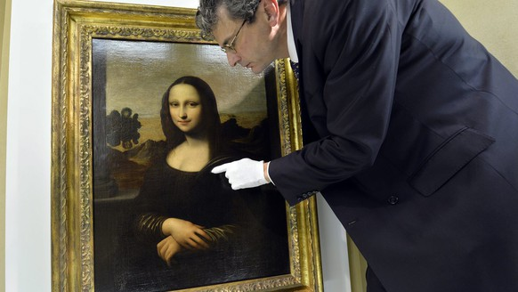 Dr Markus A. Frey, president of The Mona Lisa Foundation, poses in front of a painting attributed to Leonardo da Vinci representing Mona Lisa, displayed during a presentation, Switzerland, Thursday, November 14, 2013. The Mona Lisa Foundation, a non-profit organisation based in Zurich, presents a painting and historical, comparative and scientific evidence, which demonstrates that there have always been two portraits of the Mona Lisa by Leonardo da Vinci, the 'Earlier Version,' made ten years earlier than the 'Joconde' that is displayed in Le Louvre in Paris, France. (KEYSTONE/Martial Trezzini)