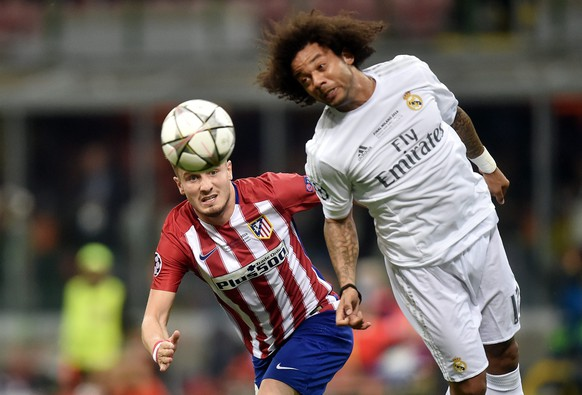epa05334606 Marcelo (R) of Real Madrid heads the ball in front of Saul Niguez of Atletico during the UEFA Champions League Final between Real Madrid and Atletico Madrid at the Giuseppe Meazza stadium in Milan, Italy, 28 May 2016.  EPA/DANIELE MASCOLO