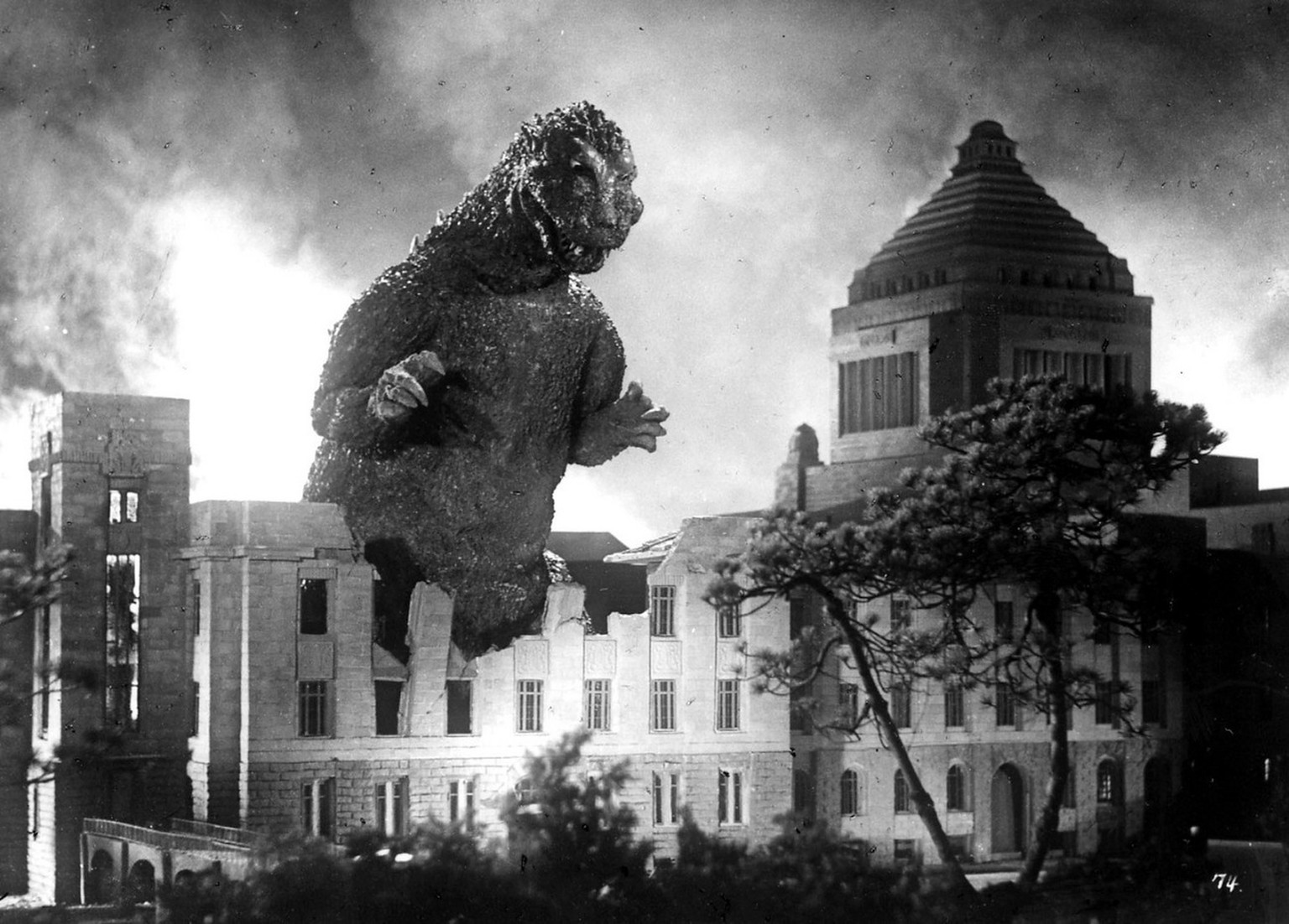 "Godzilla stomps through the Japanese Parliament building in Tokyo in the1954 debut film. Professors at the University of Kansas want people to take ""Godzilla"" more seriously. They've organized a major scholarly conference on the giant lizard-like movie monster that terrorized Tokyo. It's their way of marking the 50th anniversary of the first ""Godzilla"" film that many feel evoked the fears of the atomic age. (KEYSTONE/AP Photo/Str)   === ,  ==="