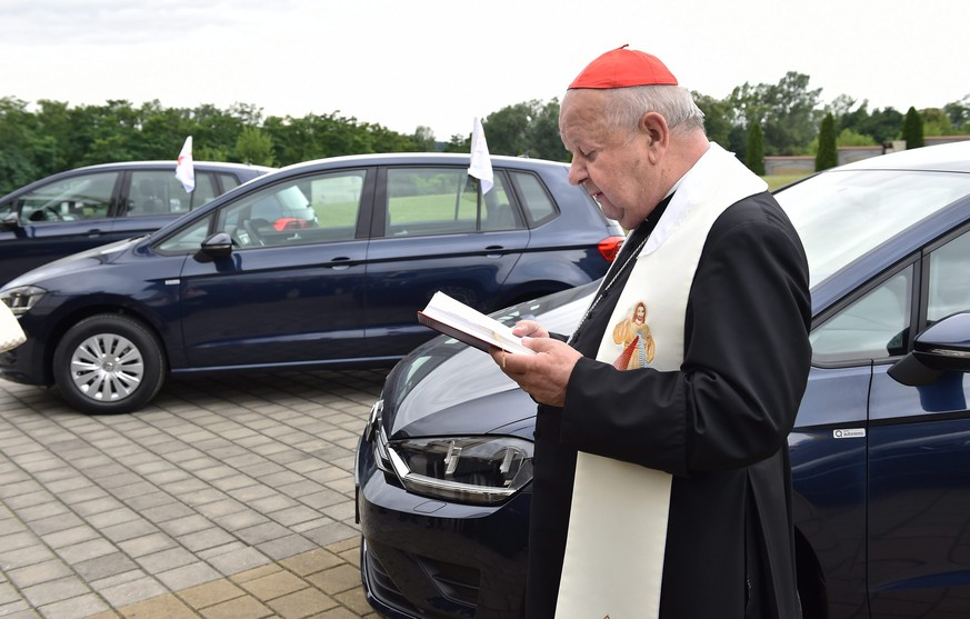 epa05426541 Cardinal Stanislaw Dziwisz stands next to a Volkswagen (VW) Golf car in front of the Divine Mercy Sanctuary in Krakow, Poland, 15 July 2016. The cars have been donated by Volkswagen to the Organizing Committee of the World Youth Day 2016. The vehicles will be available to Pope Francis when he will not be moving with the popemobile. At the end of World Youth Day, the cars will go to Caritas, a catholic charity in Krakow.  EPA/JACEK BEDNARCZYK POLAND OUT