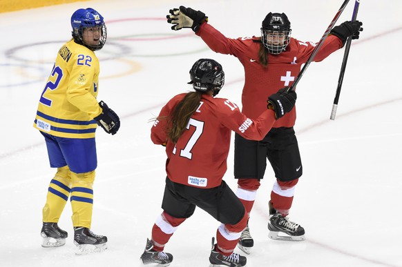Switzerland's forward Sara Benz, right, and Switzerland's forward Jessica Lutz, center, celebrate the first goal in front of Sweden's defender Emma Eliasson, left, during the women's ice hockey bronze medal game between Switzerland and Sweden at the XXII Winter Olympics 2014 Sochi in Sochi, Russia, on Thursday, February 20, 2014. (KEYSTONE/Laurent Gillieron)