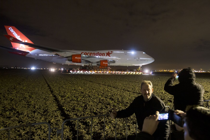 People pose for a picture as a self-propelled trailer transports a Boeing 747-400 plane through farmland from Schiphol Airport to a nearby hotel in Badhoevedorp, near Amsterdam, Netherlands, Wednesday, Feb. 6, 2019. The Boeing is making its way, hardly at jet pace, to its final resting place in the garden of a hotel on the edge of Amsterdam. The 150-ton jumbo jet will take a total of five days to cover just a few kilometers (miles). The plane was formerly owned by Dutch flag carrier KLM and is being turned into a Boeing 747 Experience by the hotel's owner, a Dutch travel company. (AP Photo/Peter Dejong)