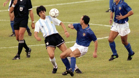 Argentina's Jose Basualdo and Italy's Salvatore Schillaci, second left, fight for the ball in the first minutes of the Soccer World Cup semi-final, in Naples, Italy, July 3, 1990. Argentina and Italy drew one all after extra and Argentina won the match in a penalty shoot-out. . (AP Photo/Lennihan)