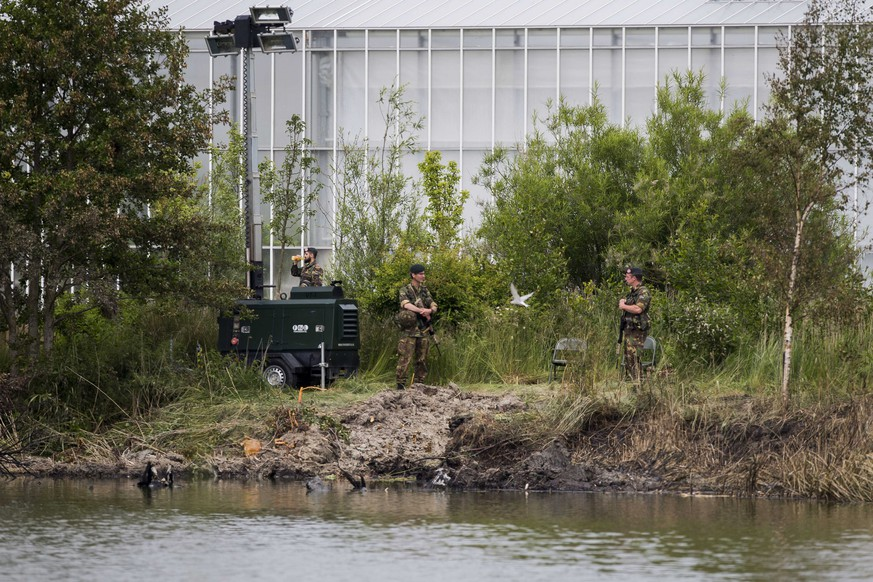 epa05355194 Dutch military guard at the crash site of the A F-5 plane of Swiss stunt team Patrouille Suisse that crashed next to a greenhouse complex in Bitgum, The Netherlands, 10 June 2016. The pilot ejected himself before the plane crash on 09 June.  EPA/VINCENT JANNINK
