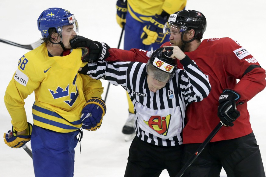 Switzerland's Timo Helbling (R) punches Sweden's Anton Lander (R) next to linesman Jon Kilian during their Ice Hockey World Championship game at the O2 arena in Prague, Czech Republic, May 9, 2015.    REUTERS/David W Cerny TPX IMAGES OF THE DAY