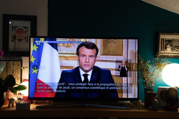 epa08299026 A TV screen shows French President Emmanuel Macron addressing the nation from the Elysee Palace about the widening coronavirus crisis, in Bois-Colombes, near Paris, France, 16 March 2020. Macron asked the French citizens to reduce their movement to the strictly necessary and postponed the second round of the Municipal Elections.  EPA/CHRISTOPHE PETIT TESSON