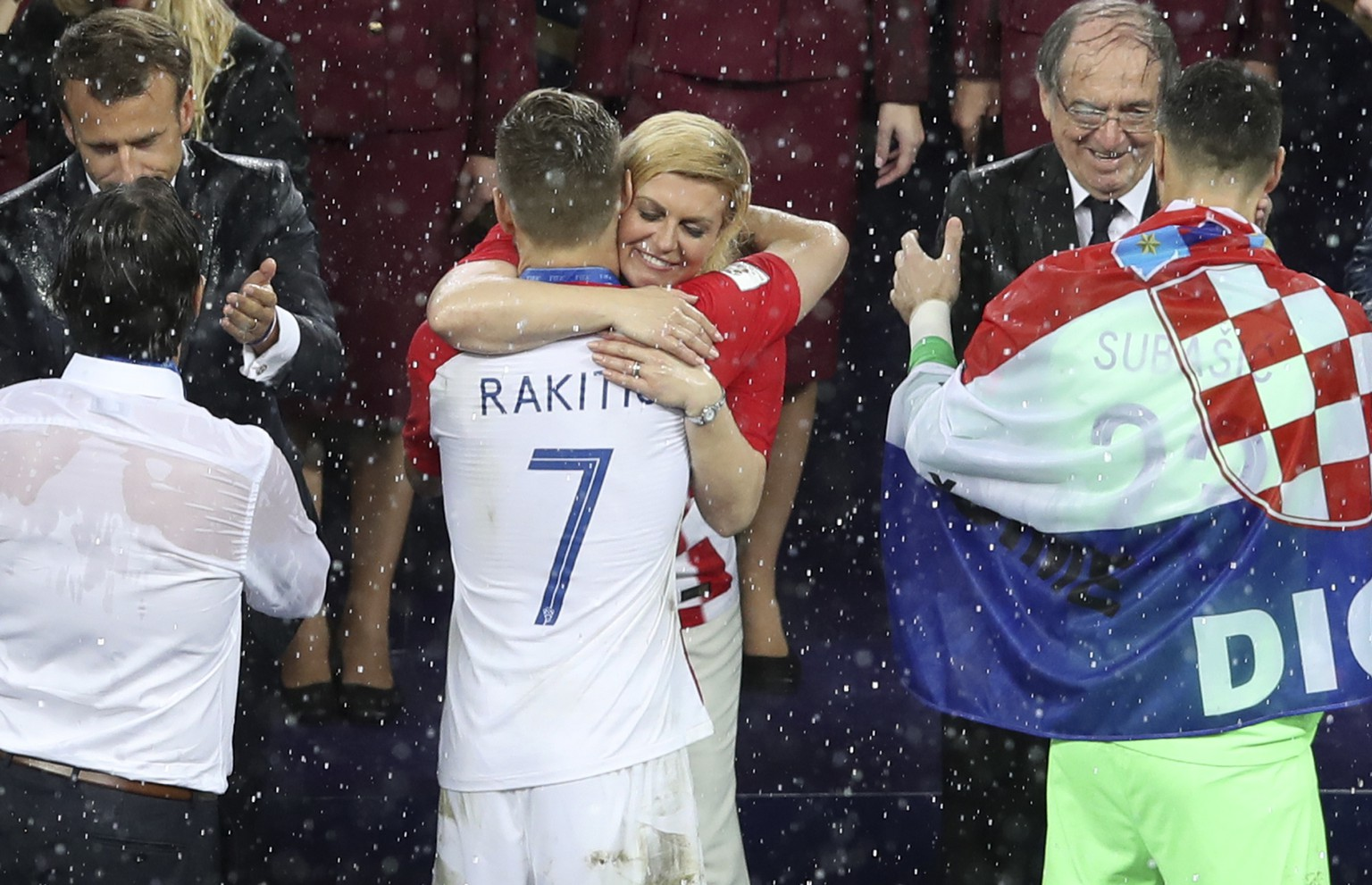 Croatian President Kalinda Grabar-Kitarovic hugs Croatia's Ivan Rakitic at the end of the final match between France and Croatia at the 2018 soccer World Cup in the Luzhniki Stadium in Moscow, Russia, Sunday, July 15, 2018. (AP Photo/Thanassis Stavrakis)