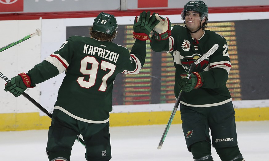 Minnesota Wild's Kirill Kaprizov (97) high-fives Kevin Fiala (22) after Kaprizov scored a goal against the St. Louis Blues during the third period of an NHL hockey game Thursday, April 29, 2021, in St. Paul, Minn. St. Louis won 5-4 in overtime. (AP Photo/Stacy Bengs)