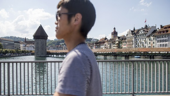 ARCHIV - ZUR TOURISMUSSTATISTIK UND DER ZUNAHME VON LOGIERNAECHTEN IN DER SCHWEIZ STELLEN WIR IHNEN DIESE BILDREPORTAGE ZUR VERFUEGUNG - The Kappelbruecke bridge in the background and an Asian tourist in foreground, in Lucerne, Switzerland, on August 14, 2017. The city of Lucerne counts between 8 and 10 million day visitors a year. (KEYSTONE/Alexandra Wey) Die Kappelbruecke im Hintergrund mit einem asiatischen Tourist auf der Seebruecke im Vordergrund, in Luzern am 14. August 2017. Die Stadt Luzern zaehlt jaehrlich zwischen 8 und 10 Millionen Tagesgaeste. (KEYSTONE/Alexandra Wey)