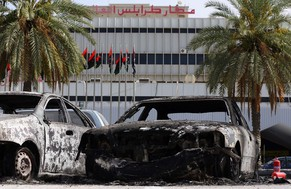 Burnt vehicles are seen in the compound of Tripoli international airport in the Libyan capital on July 14, 2014 following fighting between rival armed groups the previous day. Islamist militias attacked the rival Zintan group that controls Libya's international airport in Tripoli yesterday, triggering fierce clashes that halted flights, officials said. AFP PHOTO/MAHMUD TURKIA