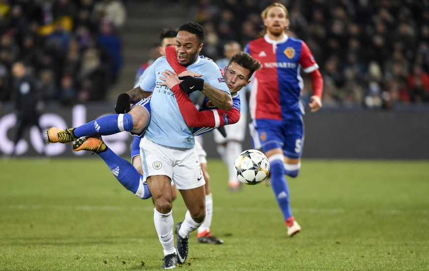 Basel's Taulant Xhaka, behind, clings to Manchester City's Raheem Sterling, front, and will get the yellow card for this action, during the UEFA Champions League round of sixteen first leg soccer match between Switzerland's FC Basel 1893 and England's Manchester City FC in the St. Jakob-Park stadium in Basel, Switzerland, on Tuesday, February 13, 2018. (KEYSTONE/Georgios Kefalas)