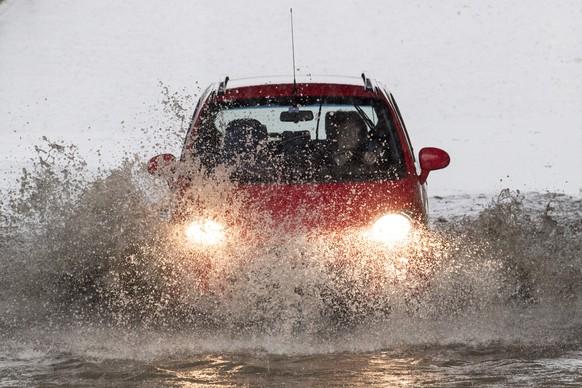 Eine Autofahrerin durchquert eine ueberflutete Strasse, aufgenommen am Mittwoch, 8. Juni 2016, in Lenzburg. Durch den starken Regen und Unwetter kam es zu Ueberschwemmungen in verschiedenen Regionen der Schweiz. (KEYSTONE/Ennio Leanza)