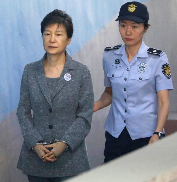 epa06161274 South Korean Former President Park Geun-hye (C) is escorted to a courtroom in Seoul, South Korea, 25 August 2017, to stand trial on alleged bribery, abuse of power and leaks of government secrets. Park, who was impeached by the Constitutional Court on 10 March, has denied all charges leveled against her.  EPA/KIM HONG-JI / POOL