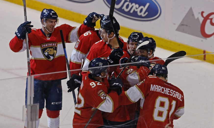 Florida Panthers players celebrate their overtime win over the New York Islanders with center Denis Malgin (obscured) who scored the winning goal in an NHL hockey game, Saturday, Nov. 12, 2016, in Sunrise, Fla. (AP Photo/Joe Skipper)