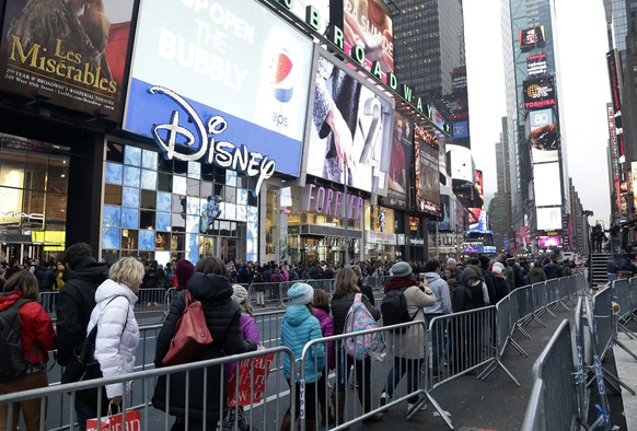 epa05084138 Pedestrians are seen walking past barricades in Times Square the day before New Year's Eve in New York, NY, USA, 30 December 2015. Thousands of people every year attend the 'Ball Drop' party in the city's famous square when an illuminated globe slides down a pole on the roof of the One Time Square building in the last minute of the old year, illuminating the New Year's number at midnight.  EPA/JASON SZENES