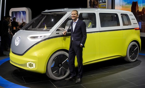 FILE - In a Jan. 9, 2017, file photo, Herbert Diess, chairman of the Volkswagen brand, poses with the I.D. Buzz all-electric concept van, at the North American International Auto Show, in Detroit. The I.D. Buzz seats up to eight and lets the driver's seat face the rear when the minivan is in self-driving mode. VW minibuses haven't been sold in the U.S. since the 1970s, but the company has released several concepts over the years that take their styling cues from the beloved minibus. (AP Photo/Tony Ding, File)