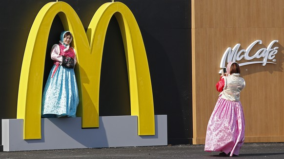 epa08175983 (FILE) - A local woman dressed in traditional clothing poses for a picture in the McDonalds arches at the Olympic Village, ahead of the start of the PyeongChang Winter Olympic Games 2018, in Gangneung, South Korea, 08 February 2018 (reissued 29 January 2020). McDonalds is to release their 4th quarter 2019 earnings report on 29 January 2020.  EPA/LARRY W. SMITH *** Local Caption *** 54095250