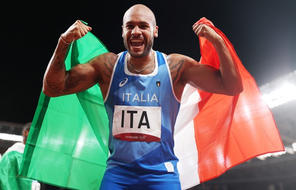 epa09401546 Lamont Marcell Jacobs of Italy celebrates after winning gold in the Men's 4x100m Relay final of the Athletics events of the Tokyo 2020 Olympic Games at the Olympic Stadium in Tokyo, Japan, 06 August 2021.  EPA/DIEGO AZUBEL