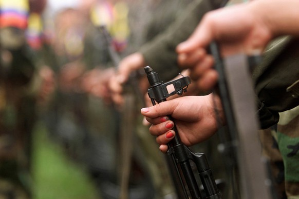 A Colombian guerilla woman holds her AK-47 as she takes part in a line of rebels during an army parade of fighters of the FARC in Villa Colombia camp near San Vicente del Caguan, Caqueta province, Colombia, April 29, 2000. REUTERS/Jose Miguel Gomez/File Photo