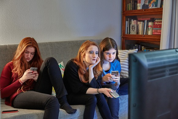 [Symbolic Image, Staged Picture, ] Sisters sitting on a couch in the living room use their smart phones while watching TV, photographed in Lucerne, Switzerland, on December 13, 2015. (KEYSTONE/Christof Schuerpf)  [Gestellte Aufnahme, Symbolbild, ] Geschwister benutzen ihre Smartphones waehrend sie im Wohnzimmer auf dem Sofa sitzend fersehen, aufgenommen am 13. Dezember 2015 in Luzern. (KEYSTONE/Christof Schuerpf)